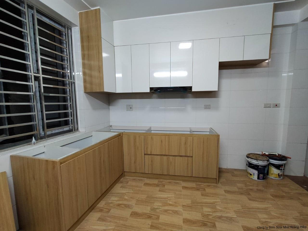 Thi công tủ bếp làm bằng chất liệu gỗ HDF cao cấp An Cường, với bè mặt phủ veneer chống chịu được ẩm ướt